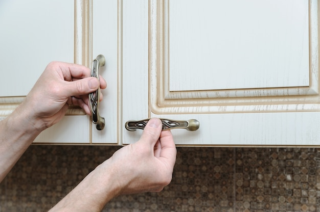Installazione di mobili da cucina e inserimento di maniglie negli armadietti