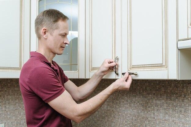 Installazione di mobili da cucina con uomo che mette le maniglie agli armadietti