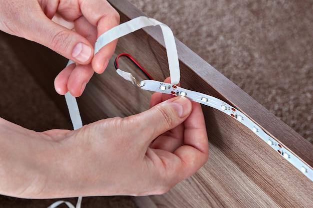 Installazione di strisce luminose a led per l'illuminazione decorativa di mobili.