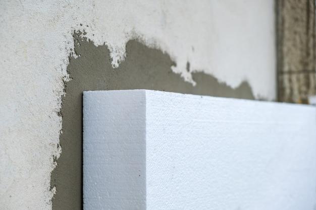 Installazione di lastre isolanti in polistirolo sulla parete della facciata della casa per la protezione termica.
