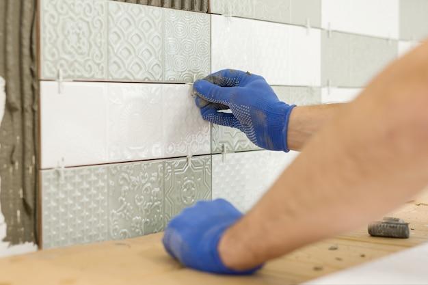 Installazione di piastrelle di ceramica sul muro in cucina