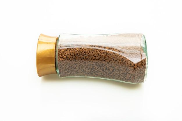 Caffè istantaneo in bottiglia di vetro isolato su sfondo bianco