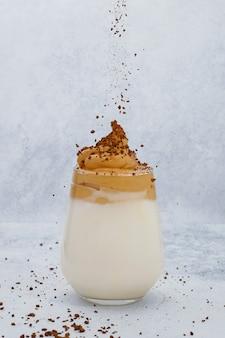 Il caffè istantaneo sta versando sulla schiuma del caffè dalgona alla moda in vetro