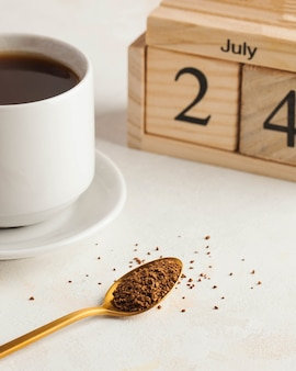 Caffè istantaneo in un cucchiaio sullo sfondo di una tazza da caffè e un calendario di legno per il compleanno di luglio ...
