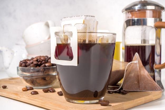 Tazza di caffè istantanea appena fatta dal sacchetto. varietà alla moda di caffè a goccia, sul tavolo da cucina bianco con tazze, spazio copia
