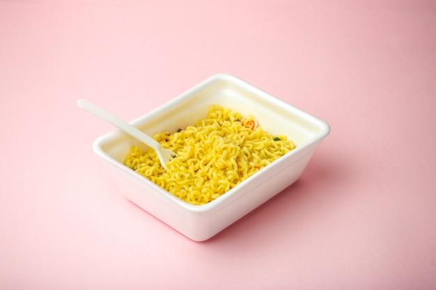 Noodles istantanei su uno sfondo rosa minimo in una scatola di plastica. concetto di fast food e cibo spazzatura. concept minimal creativo.