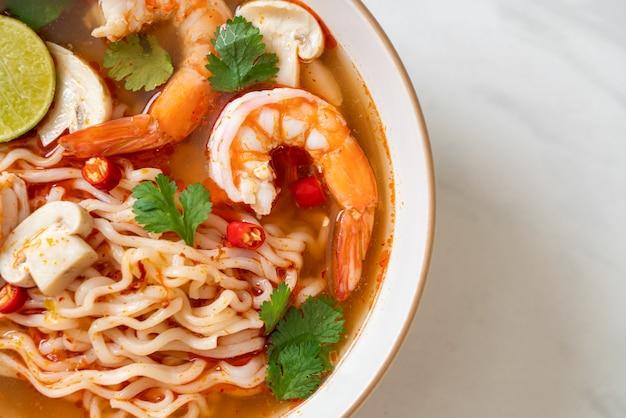 Spaghetti istantanei ramen in zuppa piccante con gamberetti (tom yum kung) - stile di cibo asiatico