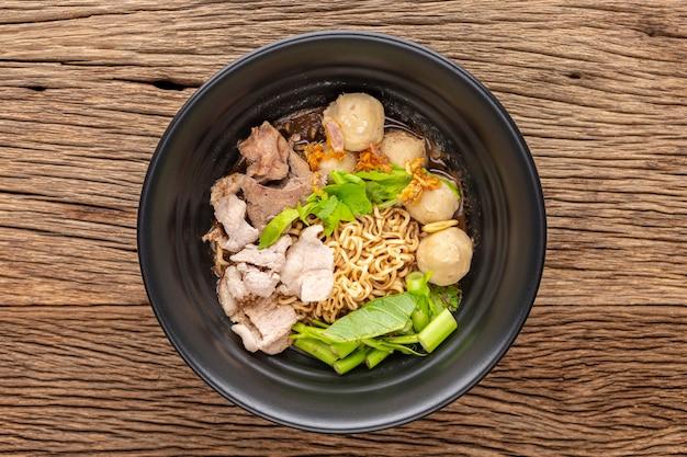 Zuppa di noodles istantanei con manzo, polpetta, fegato di maiale, spinaci d'acqua, gloria mattutina, sedano, aglio fritto ed erbe in una ciotola di ceramica nera su fondo rustico in legno, vista dall'alto