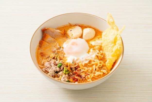 Spaghetti istantanei con maiale e polpette in zuppa piccante o tom yum noodles in stile asiatico