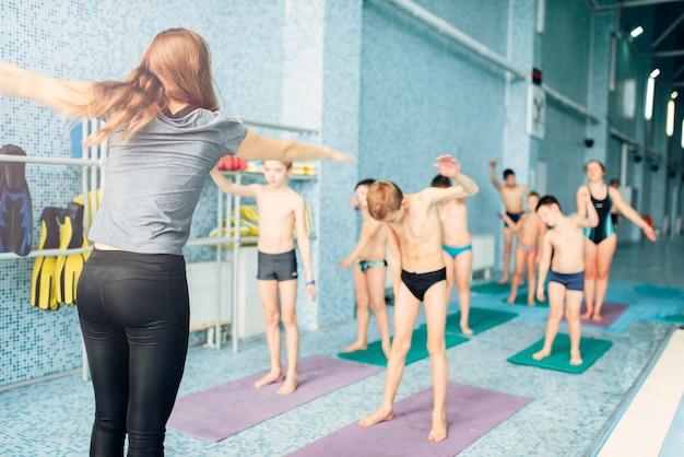 Istruttore e gruppo di bambini che fanno esercizi