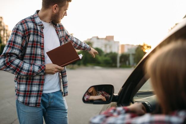 L'istruttore sostiene l'esame, studente sul terreno di guida