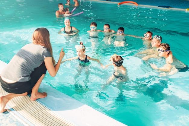 L'istruttore insegna ai bambini a nuotare