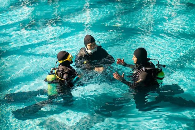 Istruttore e due subacquei in autorespiratore, corso sub in scuola sub. insegnare alle persone a nuotare sott'acqua con l'attrezzatura subacquea, l'interno della piscina coperta sullo sfondo, l'allenamento di gruppo