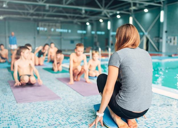 Istruttore con bambini che fanno esercizi