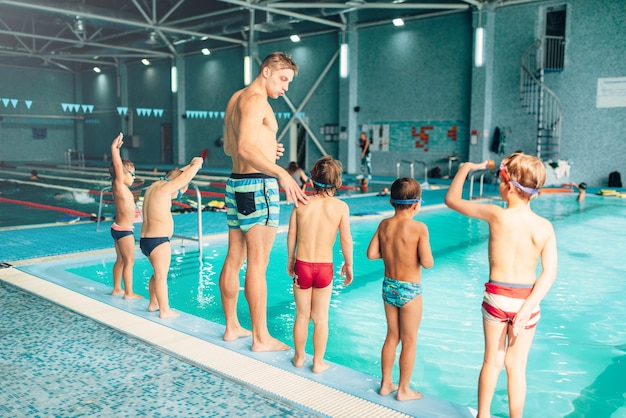 Istruttore con bambini si trova vicino all'acqua