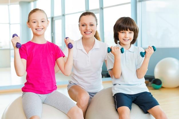 Istruttore con i bambini. istruttore allegro che aiuta i bambini a fare esercizio nel centro benessere
