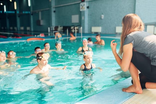 L'istruttore lavora con i bambini in piscina