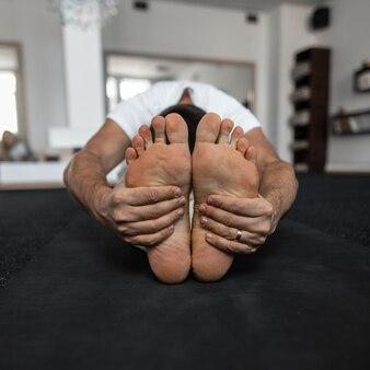 Il giovane istruttore si siede nella posizione del loto e medita. l'allenatore fa yoga. primo piano dei piedi nudi maschili.