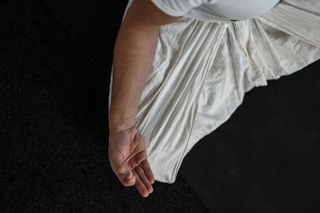 Il giovane istruttore si siede nella posizione del loto e medita. l'allenatore fa yoga. vista dall'alto. avvicinamento.