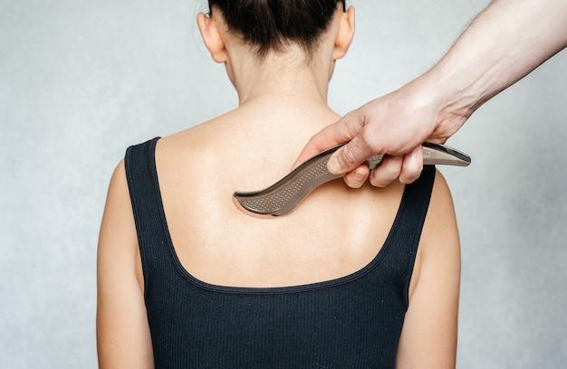Mobilizzazione strumentale dei tessuti molli una donna che riceve un trattamento dei tessuti molli sulla schiena con...