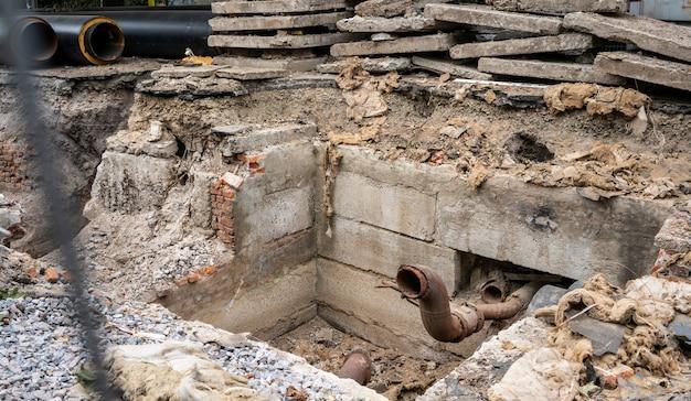 Tubi isolati e lastre di cemento in trincea all'aperto.