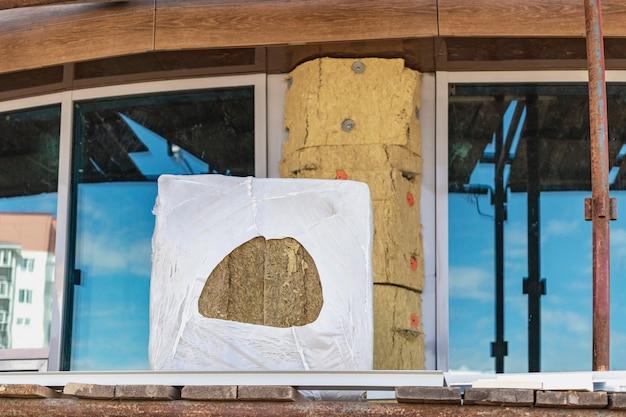 Isolamento della facciata dell'edificio con lana minerale. l'imballaggio della lana minerale spetta agli apprendisti edili. insonorizzazione e isolamento.