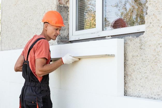 Isolamento della casa con polyfoam. l'operaio sta controllando con un righello di intonaco di alluminio la precisione dell'installazione di un pannello di polistirolo sulla facciata.