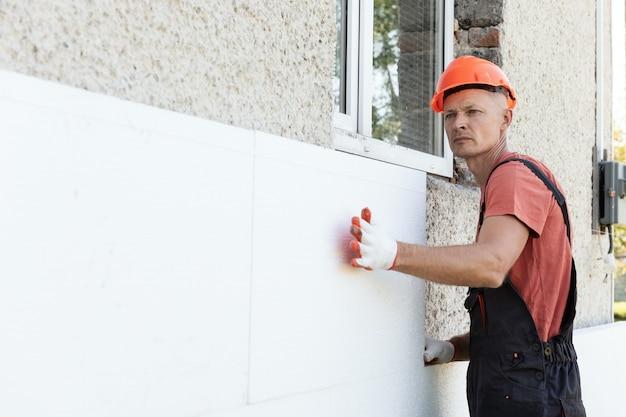Isolamento della casa con polyfoam. il lavoratore sta installando un pannello di polistirolo sulla facciata.