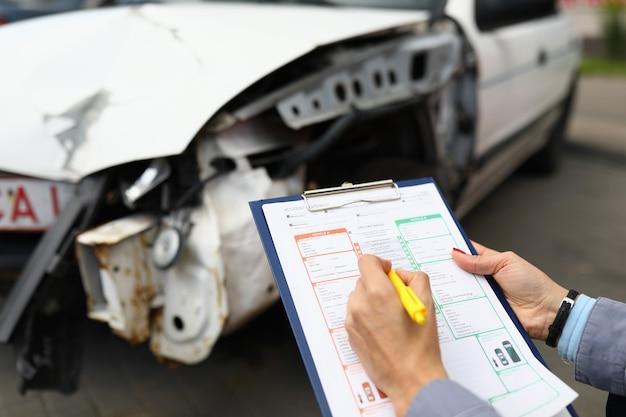 L'agente di assicurazione tiene il primo piano della penna a sfera e della lavagna per appunti e dell'automobile distrutta nella priorità bassa