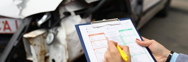 L'agente di assicurazione tiene il primo piano della penna a sfera e della lavagna per appunti e l'auto distrutta. concetto di assicurazione del veicolo.