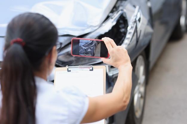 L'agente assicurativo sta filmando i danni alle conseguenze dell'auto del concetto di incidente stradale