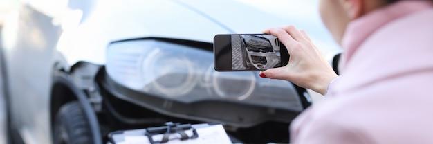 Agente assicurativo che fotografa la stima del primo piano dell'auto distrutta del costo dell'auto danneggiata