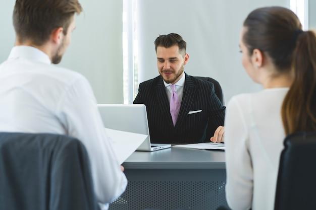 Broker assicurativo o venditore che fa un'offerta a una giovane coppia millenaria utilizzando il laptop in un bar, agente immobiliare che consulta i clienti sul mutuo seduto al tavolo del caffè che punta sullo schermo del computer.
