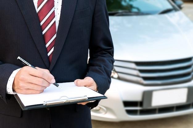 Un impiegato esperto di assicurazioni che lavora con un'auto all'aperto