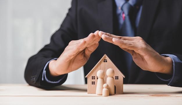 Casa di assicurazione e concetto di salute della famiglia dal vivo. l'agente assicurativo presenta il modello ้di protezione delle mani che simboleggia la copertura.