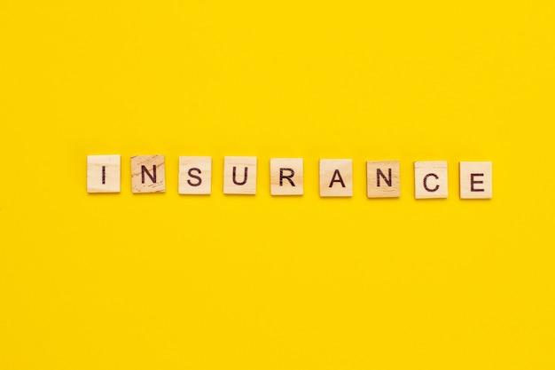 Iscrizione di assicurazione da cubi di legno su sfondo giallo