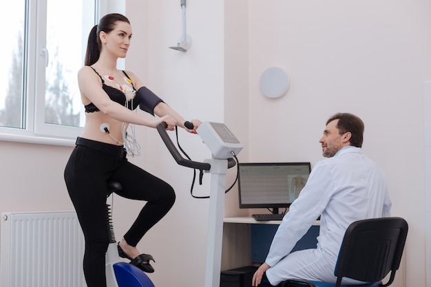 Cardiologo di spicco curioso intelligente che studia l'impatto dell'esercizio fisico sulla giovane donna controllando il suo sistema cardiovascolare utilizzando alcune attrezzature speciali