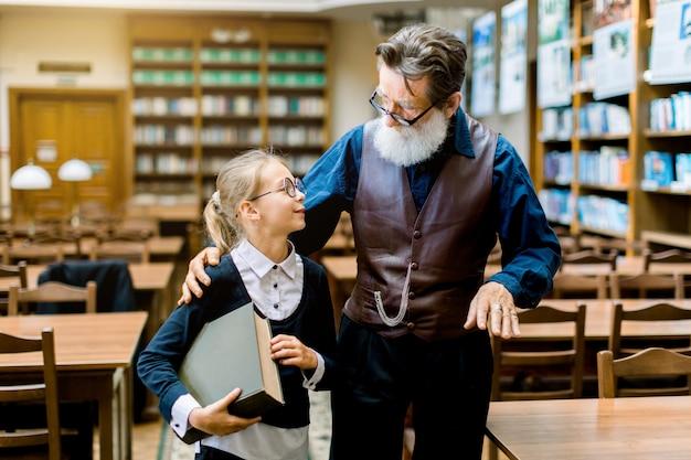 Intelligente bibliotecario uomo anziano con barba grigia, che indossa abiti eleganti e alla moda, abbraccia una ragazza adolescente piuttosto bionda che visita la biblioteca per ottenere conoscenza