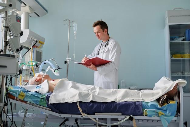 Il medico caucasico di terapia intensiva esamina le note intubate di scrittura del paziente di posizione critica al caso clinico nel reparto di terapia intensiva