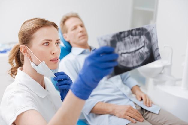 Intento attento dentista addestrato che osserva la scansione della linea della mascella dei suoi pazienti e lavora allo sviluppo della diagnosi e delle strategie di trattamento