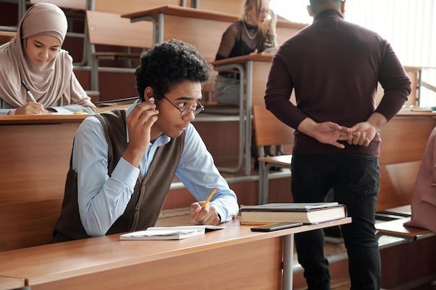 Ragazzo interculturale in abbigliamento casual che mette l'auricolare nell'orecchio destro dietro la schiena dell'insegnante mentre è seduto alla scrivania durante il lavoro individuale a lezione