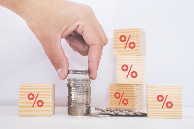 Tasso di interesse finanziario e concetto di risparmio. mano che mette le monete in una pila con monete e simbolo di percentuale.