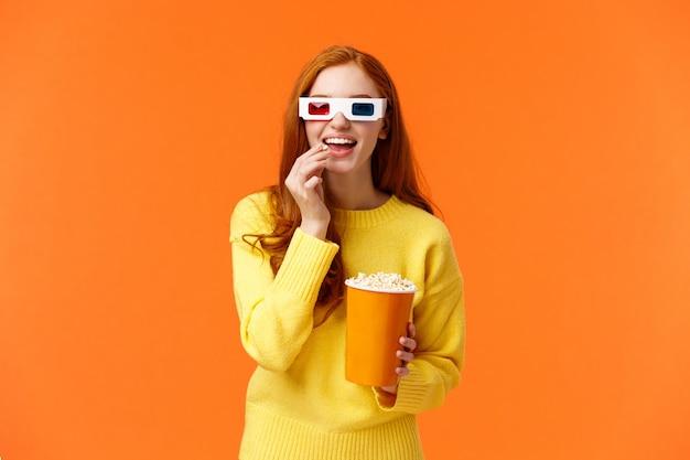 Donna rossa geniale e sorridente interessata e divertita in maglione giallo, guardando film al cinema con gli occhiali 3d, mangiando popcorn