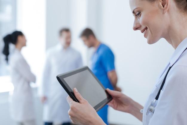 Infermiera affascinante felice interessata in piedi nella clinica e tenendo il tablet mentre i suoi colleghi hanno conversazione dietro