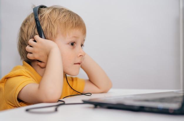 Un piccolo scolaro interessato in cuffia è seduto a un tavolo di casa e guarda un video tutorial