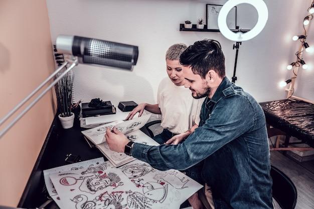 Disegni interessanti. cliente dai capelli scuri con il suo maestro femminile che sfoglia l'album con schizzi e sceglie il disegno del tatuaggio