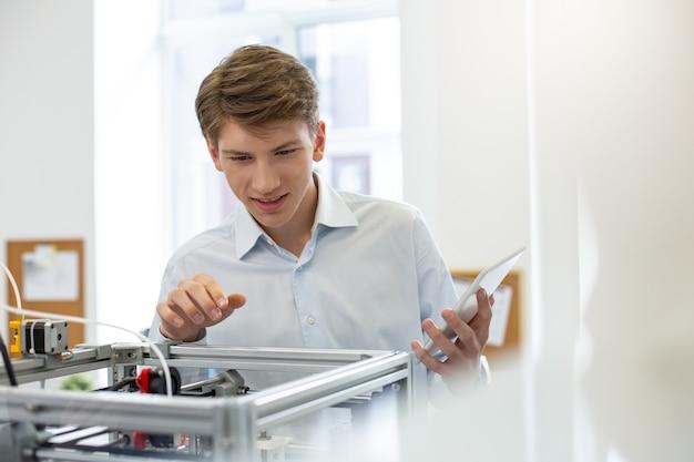 Scoperta interessante. affascinante giovane impiegato che sorride piacevolmente mentre sbircia all'interno della stampante 3d e scopre qualcosa di nuovo sul suo meccanismo