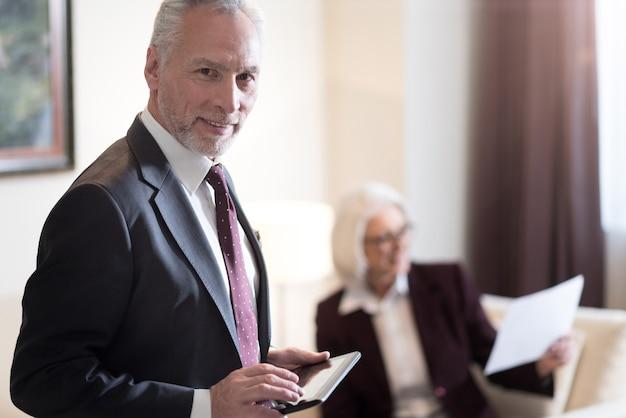 Gadget interessante. uomo d'affari invecchiato felice allegro che sorride e che tiene il tablet mentre si trovava in ufficio e il suo collega che lavora con i documenti