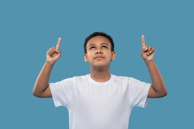 Interessante qui. scolaro ragazzo carino dalla pelle scura che guarda e punta con il dito indice verso l'alto su sfondo blu