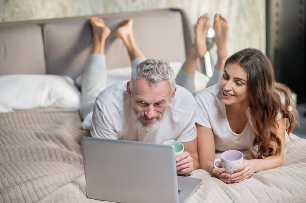 Interessante qui. sorridente uomo barbuto interessato e donna dai capelli lunghi con caffè sdraiato davanti al computer portatile sul letto
